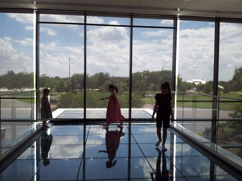 Kids walking on glass floor at Wichita Art Museum 2nd floor
