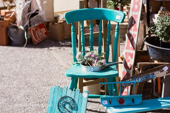 Cute repurposed blue painted chair at outdoor market.