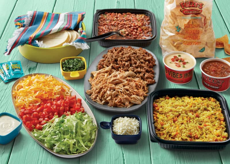 Family meal for Easter from Fuzzy's Taco shop: various Mexican food dishes arranged on a green background