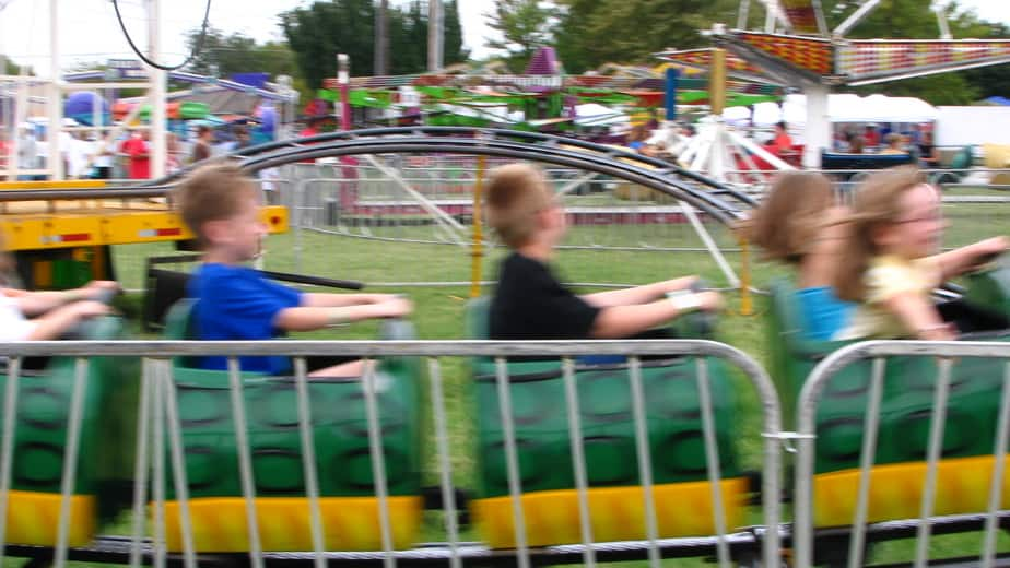 carnival at fall festival - blurred image of kids roller coaster with other rides in the background