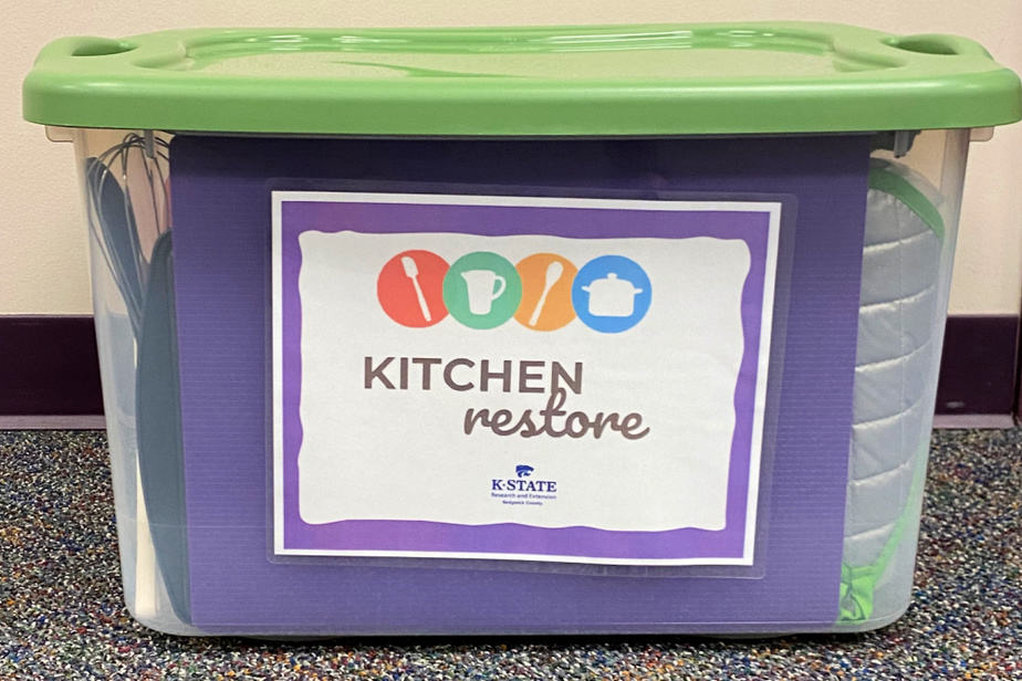 Starter Kit of donated kitchen supplies inside a covered plastic tub