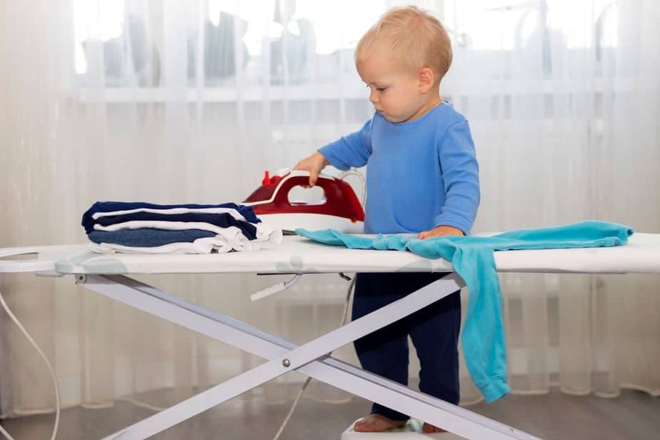 Little boy much too young ironing