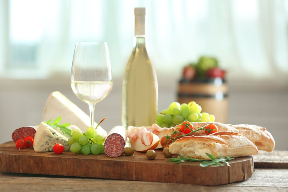 elegant charcuterie board with meats, cheeses, bread, glass of wine and wine bottle