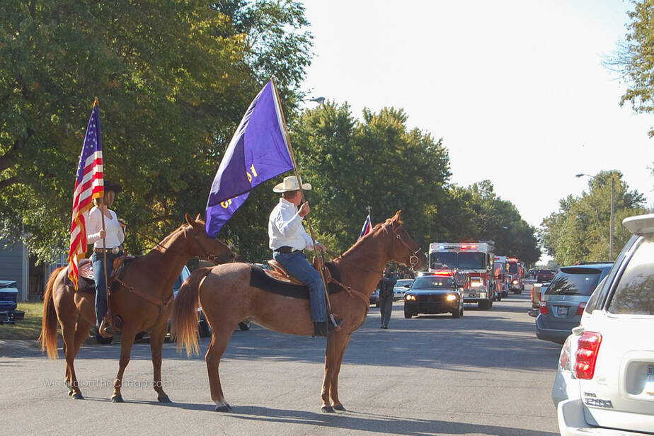 Leaders of the parade on horseback with the American and Kansas flags