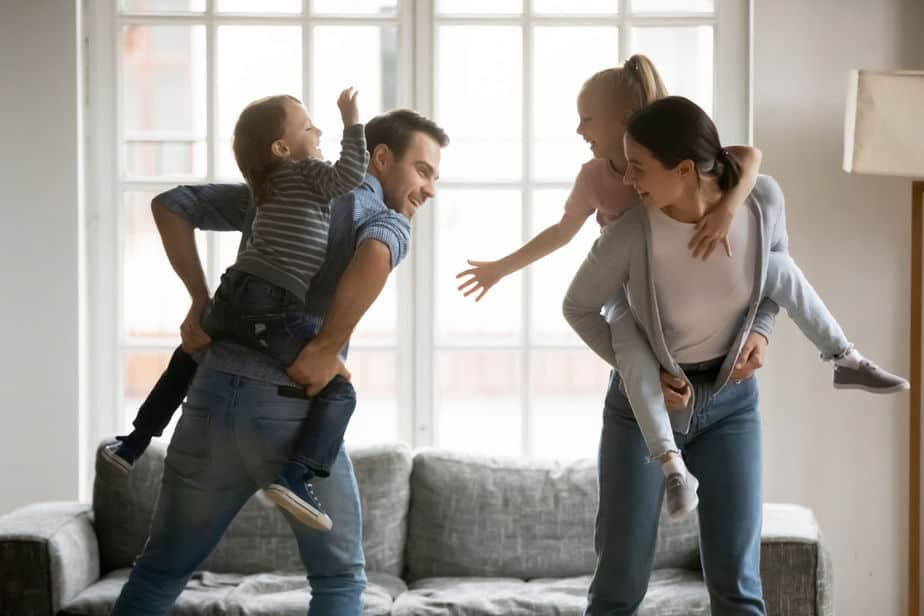 family playing together - parents carrying kids piggyback playing game