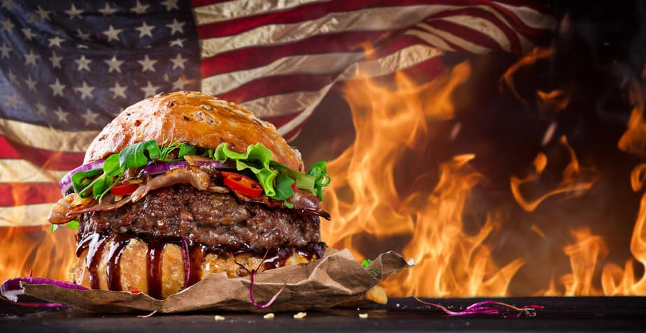American flag behind delicious-looking flame-broiled hamburger with lettuce and tomato on a bun
