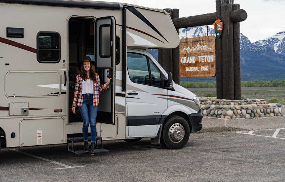 Woman standing in door of rented RV with mountains in the background
